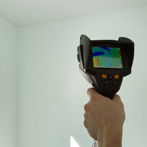 A Plumber Aims a Thermal Imaging Device at a Wall to Detect Leaks.