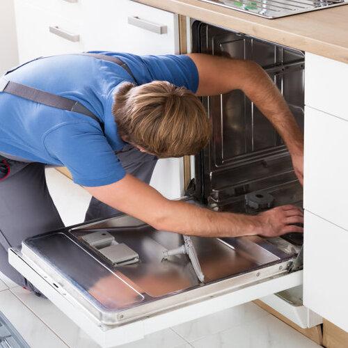 Man repairing a dishwasher.